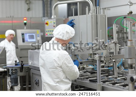 two workers in white uniforms at production line in plant - stock photo