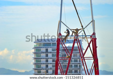 Two workers install a lot of Metal tiered tower - stock photo
