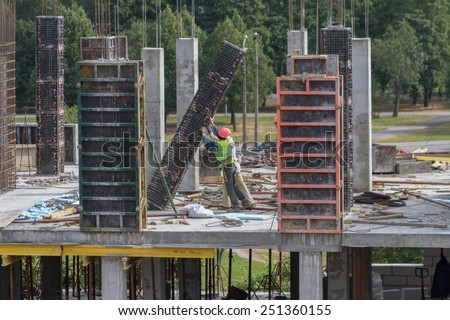Two workers of the builder in helmets push a plate on building of the new house - stock photo