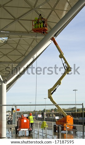 Two workers on a lift, repairing some platform. London, UK. - stock photo
