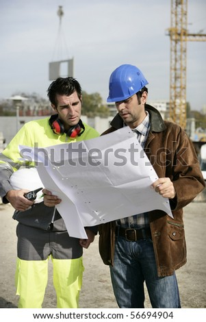 Two workers reading a plan - stock photo