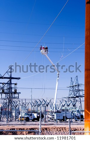 Two workers repairing high power wires. - stock photo