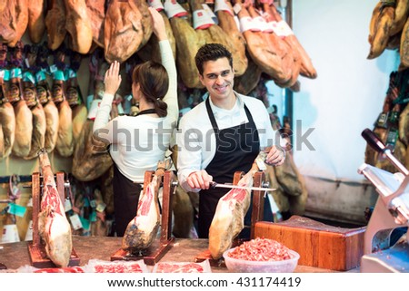 Two workers selling jamon and smiling in grocery store