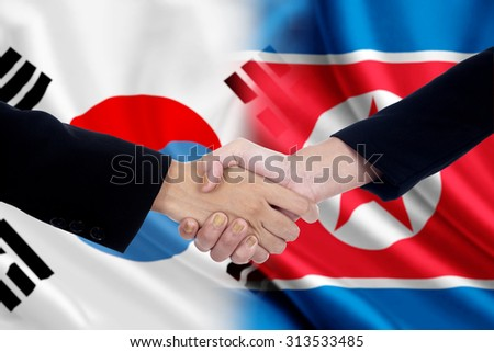 Two workers shaking hands after negotiation in front of the north and south korean flags - stock photo
