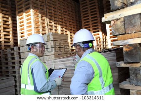 two workers talking beside on stacking pallet with holding notes - stock photo