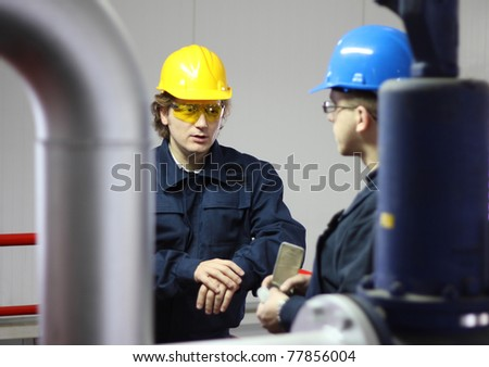 Two workers talking in a factory - stock photo