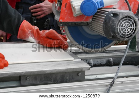 two workers using a tilesaw to saw tiles