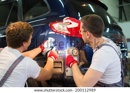 Two workers with colour samples choosing correct shade in a car body workshop  - stock photo