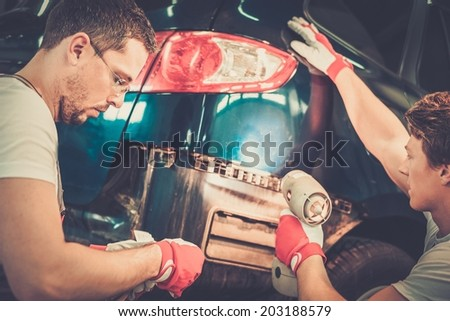 Two workers with colour samples choosing correct tone in a car body workshop  - stock photo