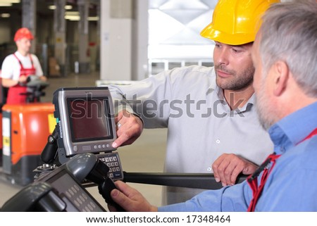 two workers with control panel in factory, third one on forklift in background - stock photo