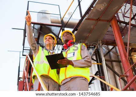 two workers working at petrochemical plant - stock photo