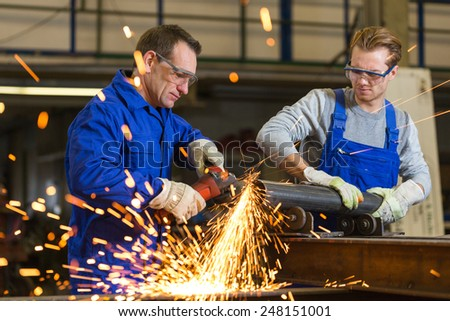 Two workers working with angle grinder in steel construction - stock photo
