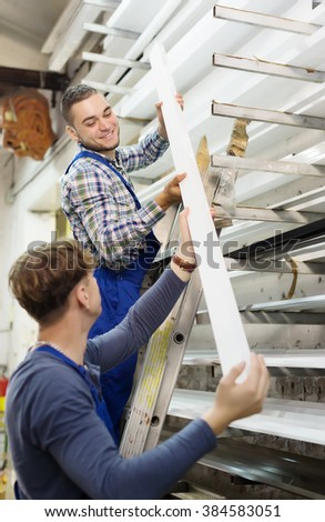 Two workers working with  window profile at stand - stock photo