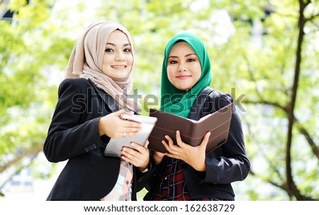two working muslim woman have discussion at beautiful park - stock photo