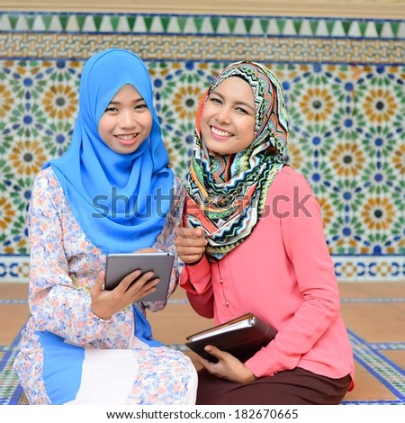 two working muslim woman have discussion at beautiful park
