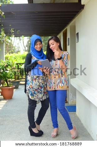 Two working muslim woman have discussion with mobile tablet - stock photo