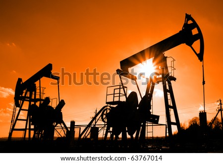 two working oil pumps silhouette against sun