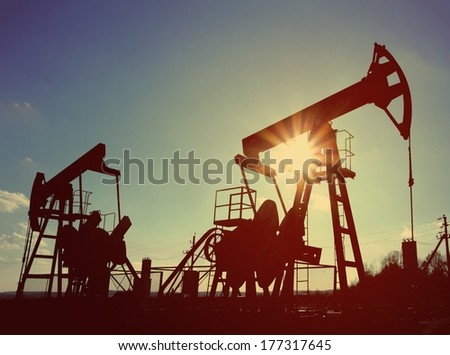two working oil pumps silhouette against sun - vintage retro style