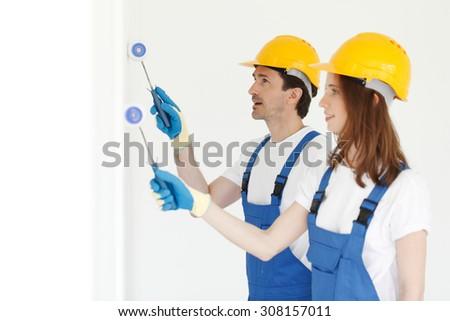 two workmen painting white wall - stock photo