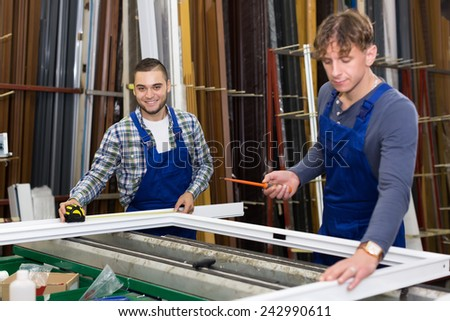 Two workmen working with window profiles at indusrty plant - stock photo