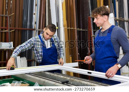 Two workmen working with window profiles at  plant - stock photo