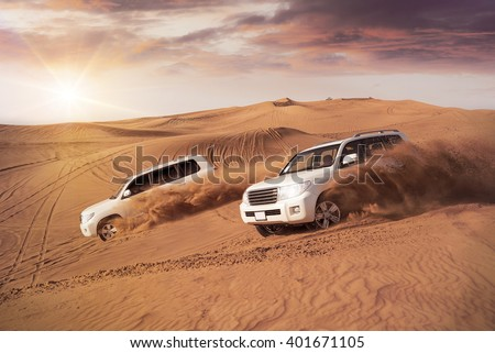two 4x4 vehicles bashing side to side through the desert dunes in the evening sun - stock photo