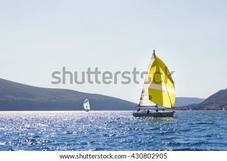 "Two yachts on calm water. Tivat, Montenegro - 26 April, 2016. Regatta ""Russian stream"" in God-Katorskaya bay of the Adriatic Sea off the coast of Montenegro. - stock photo"