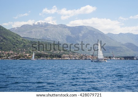 """Two yachts on the background of the coast. Tivat, Montenegro - 24 April, 2016 Regatta """"Russian stream"""" in God-Katorskaya bay of the Adriatic Sea off the coast of Montenegro. - stock photo"""