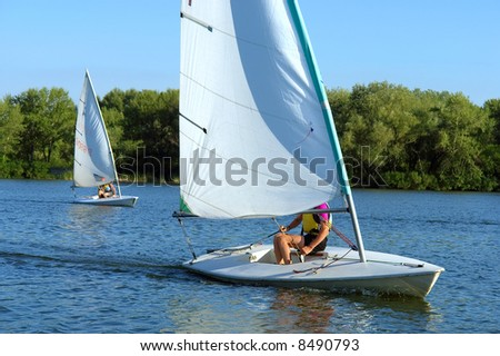 Two yachts race on river. Shot in July, Dnieper river, Ukraine. - stock photo