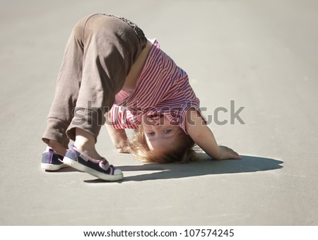 Two-year chid looks around, upside down - stock photo