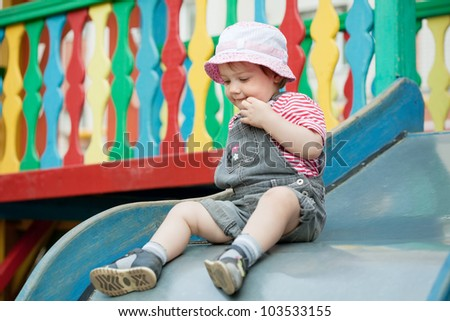 two-year child on slide playground area