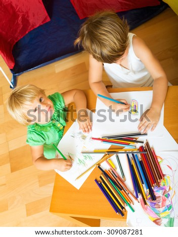 Two year children sketching on paper in home interior