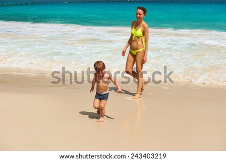 Two year old baby boy and his mother playing on beach at Seychelles - stock photo