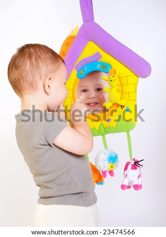 Two year old baby boy enjoys playing with toys. Studio Shot. All toys visible on the photo are officially property released.
