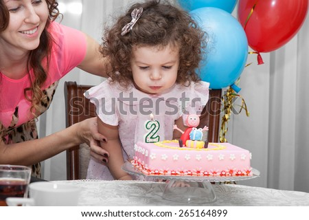 Two year old baby girl blows out candles on cake on his birthday, her happy mom in the background