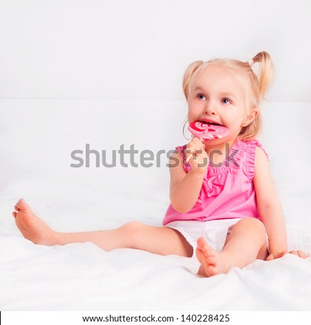 two year old blond girl eating a candy in bed at home - stock photo