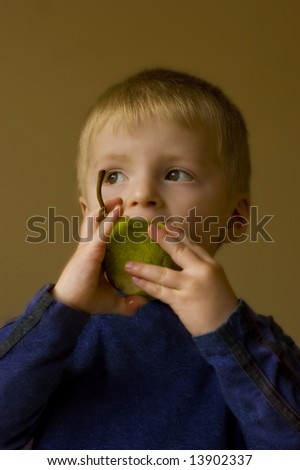 Two year old boy eating a delicious pear - stock photo