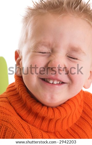 Two year old boy keeping his eyes firmly shut while laughing - stock photo