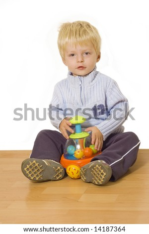 Two year old boy playing with a musical push-toy on wooden floor - stock photo