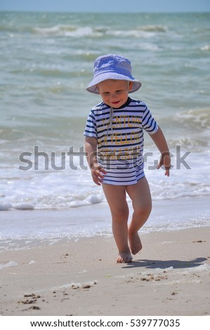 two-year-old boy run on the beach along the coast with strong waves