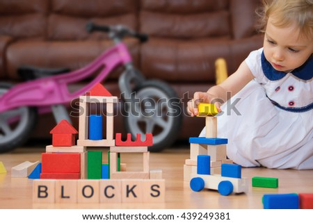 Two-year old caucasian girl playing with wooden blocks. - stock photo