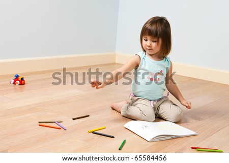 Two year old cute girl paints with color felt-tip pen in a room - stock photo