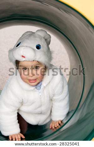 Two year old girl in a bunny hat and faux fur coat is crawling through a tube on a playground looking at the viewer. - stock photo