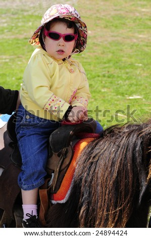 Two year old girl rides a pony on nice summer day in Marin County, San Francisco Bay Area, California. - stock photo