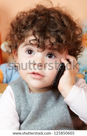 Two year old girl with curly hair talking on phone. - stock photo