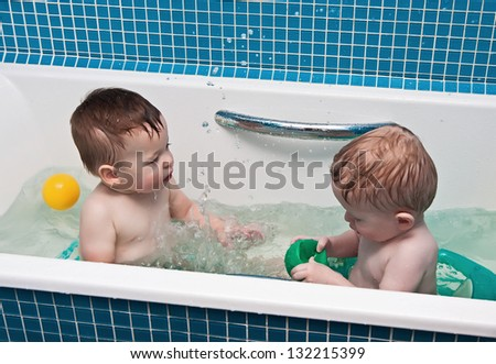 Two-year-old twins play a bathroom - stock photo