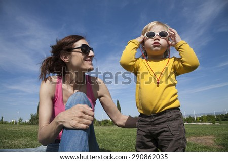 two years aged blonde happy baby yellow shirt with white kid sunglasses next to brunette woman mother smiling sitting on green grass lawn in park - stock photo