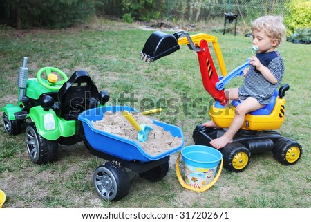 two years old baby boy playing with his excavator toy in a garden - stock photo