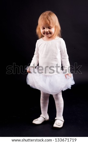Two years old baby girl wearing white suit at black background.