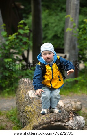 two years old boy on a trunk of a tree - stock photo